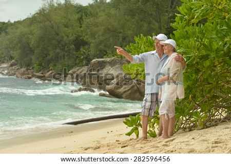 Beautiful happy elderly couple walking along the seashore