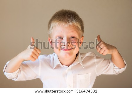 beautiful, happy, excited and confident boy showing thumbs up over grey background - stock photo