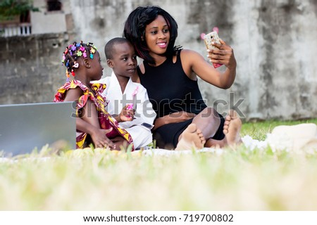 beautiful happy family at the park, mother and two children taking a picture with a mobile phone