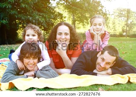 Beautiful happy family enjoying the outdoor park. - stock photo