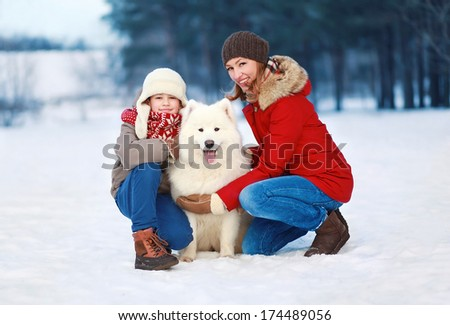 Beautiful happy family, mother and son walking with white Samoyed dog outdoors in winter day - stock photo