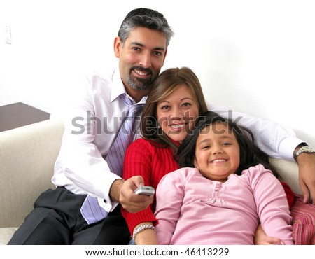 Beautiful happy family with TV remote control
