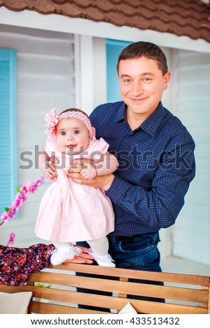 Beautiful happy father with adorable daughter cute smiling girl on the background of country house on the bench. Happy childhood. Background, macro, closeup - stock photo