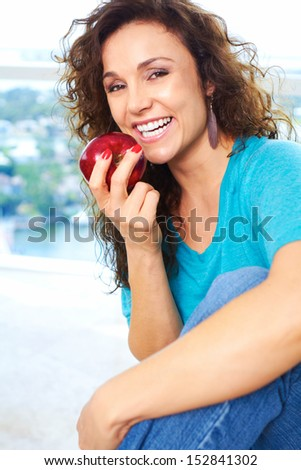 Beautiful happy female eating an apple - stock photo