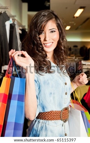 Beautiful happy female in a store holding shopping bags in both hands - stock photo