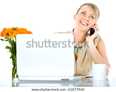 Beautiful happy female sitting behind desk with laptop, talking on the phone - stock photo