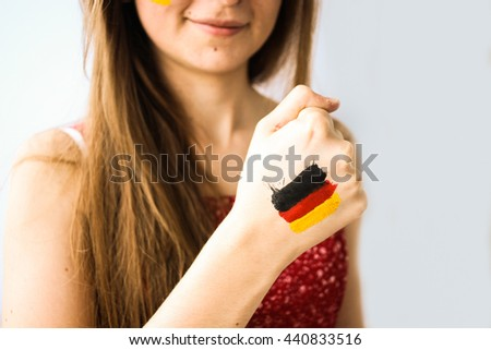 Beautiful happy german football fan with flag painted on hands and face closeup - stock photo