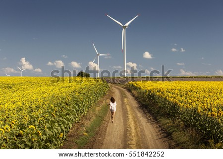 Beautiful happy girl enjoying time on the road in the middle of sunflowers landscape