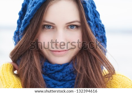 beautiful happy girl in yellow sweater and blue scarf - stock photo