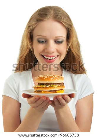 beautiful happy girl looks at a plate of fast food, hamburger isolated on white background