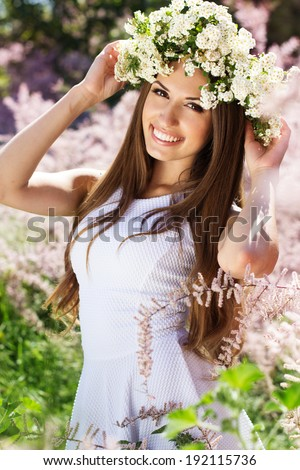 Beautiful happy girl on the nature in wreath of white flowers - stock photo