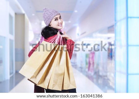 Beautiful happy girl with shopping bags in shopping mall
