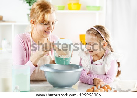 Beautiful happy grandmother learning her granddaughter Baking in a kitchen.  - stock photo