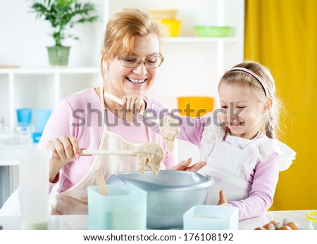 Beautiful happy grandmother learning her granddaughter how to making Dough in the kitchen. - stock photo