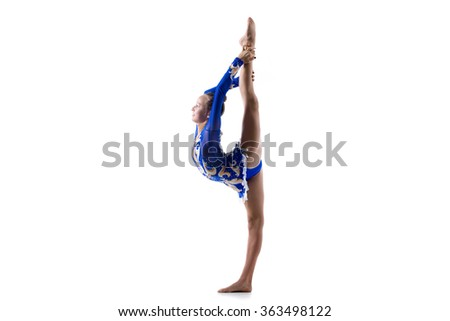 Beautiful happy gymnast athlete teenage girl wearing dancer blue dress working out, dancing, posing, doing back scale, balance gymnastics exercise, standing splits, studio, white background, isolated - stock photo