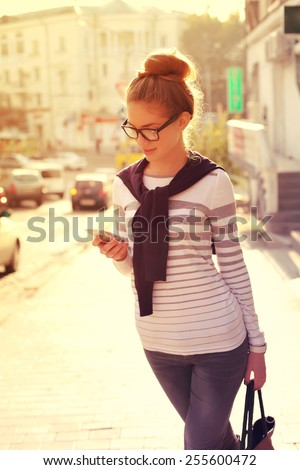 Beautiful happy hipster girl goes shopping in the city. Closeup of trendy girl face. Photo toned style instagram filters - stock photo