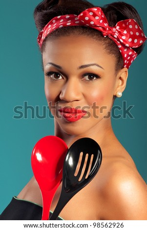Beautiful happy joyful pinup style housewife with kitchen utensils