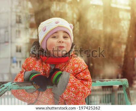 Beautiful happy kid in the red jacket in the winter outdoors. - stock photo