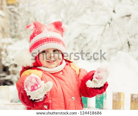 Beautiful happy kid in the red jacket in the winter outdoors shows mittens. - stock photo