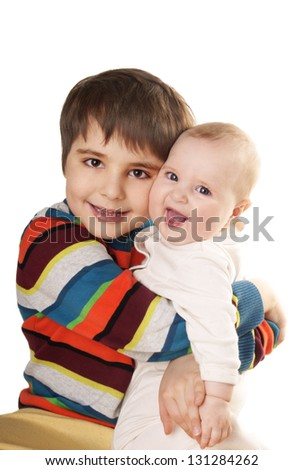 Beautiful happy kids: smiling young brother and and laughing baby sister in a hug. Isolated on a white background. - stock photo