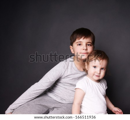 Beautiful happy kids: smiling young brother and and laughing baby sister in a hug, studio shot - stock photo