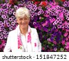 Beautiful happy lady in her seventies in front of petunia flowers.  - stock photo