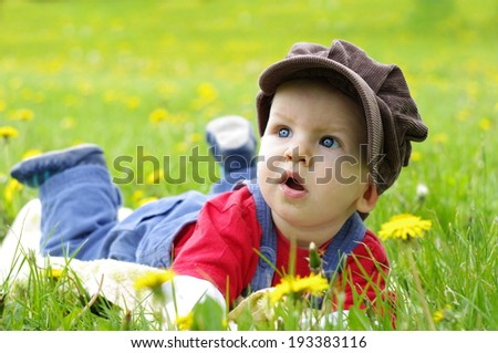 Beautiful happy little baby boy in hat on a green meadow with yellow flowers dandelions on the nature in the park. Allergy concept