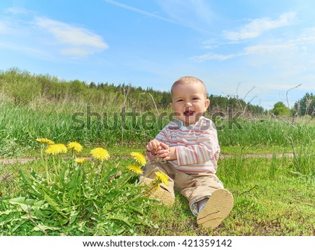 Beautiful happy little baby boy sitting on a green meadow with yellow flowers dandelions on the nature - stock photo