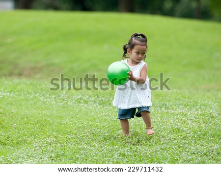 Beautiful happy little baby girl sitting on a green meadow in the park  - stock photo
