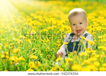 Beautiful happy little baby girl sitting on a green meadow with yellow flowers dandelions on the nature in the park - stock photo