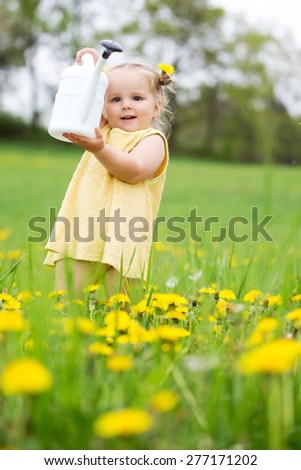 Beautiful happy little baby girl with a wreath on a meadow between yellow flowers dandelions showing a white sprinkler - stock photo