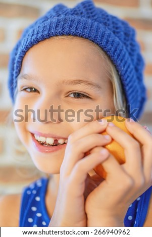 Beautiful happy little girl in blue beret smile with orange. - stock photo