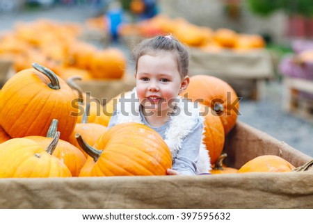 Beautiful happy little kid girl on a pumpkin farm with huge vegetables. Child celebrating traditional festival halloween or thanksgiving.