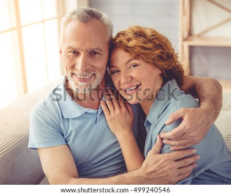 Beautiful happy mature couple is hugging, looking at camera and smiling while sitting on couch at home