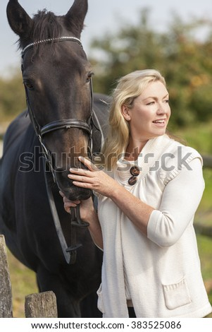 Beautiful happy middle aged woman smiling and stroking her horse outside in sunny field