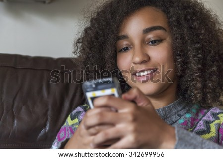 Beautiful happy mixed race African American girl teenager female child smiling with perfect teeth and texting sending text message on cell phone - stock photo