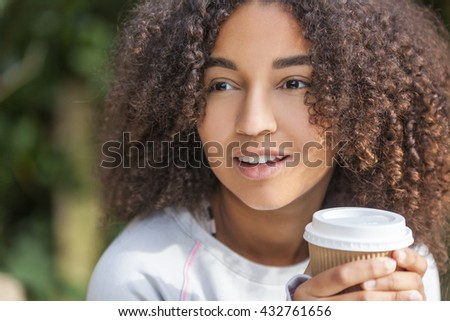 Beautiful happy mixed race African American girl teenager female young woman smiling drinking takeaway coffee outside  - stock photo