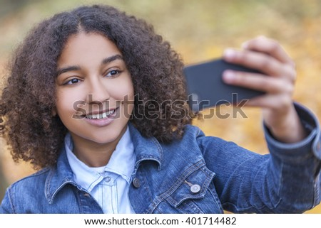 Beautiful happy mixed race African American young woman girl teenager female child smiling with perfect teeth taking selfie photograph in fall or autumn - stock photo