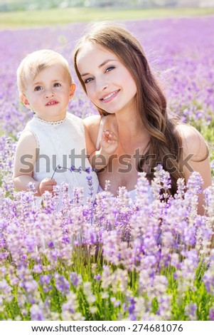 Beautiful happy mother and daughter playing in lavender field on beautiful summer day - stock photo