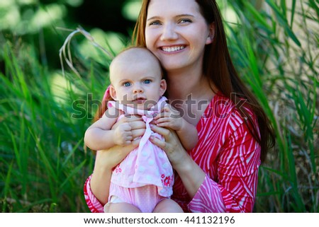 Beautiful happy mother holding baby girl with love outdoors summer background. Closeup tender portrait - stock photo