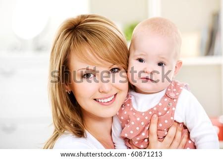Beautiful happy mother holding  newborn baby on hands - Indoors - stock photo