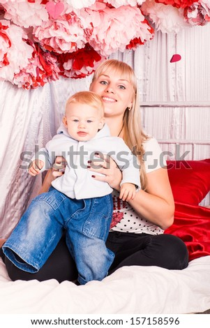 Beautiful happy mother hugging a baby on a bed in the bedroom