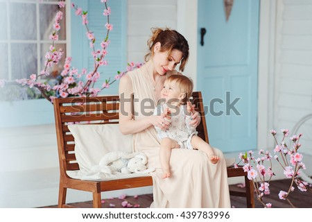 Beautiful happy mother with adorable daughter cute smiling girl on the background of spring country house on the bench. Happy childhood.  - stock photo