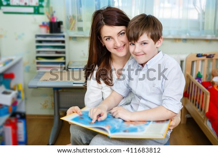 Beautiful happy mother with child boy 10 years old reading book, sitting on chair in children's room at home - stock photo