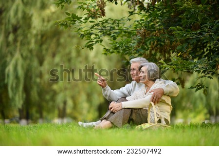 Beautiful happy old people sitting in the summer park. man pointing - stock photo