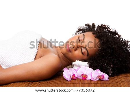 Beautiful happy peaceful sleeping Brazilian woman at a day spa, laying on bamboo massage table with head on pillow wearing a towel and orchid flowers around, isolated. - stock photo