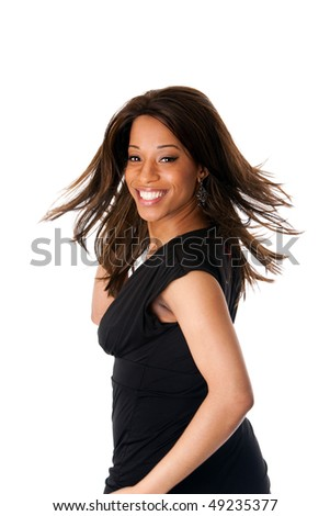 Beautiful happy smiling African American business woman in black dress swirling and twirling her long hair while turning head, isolated.