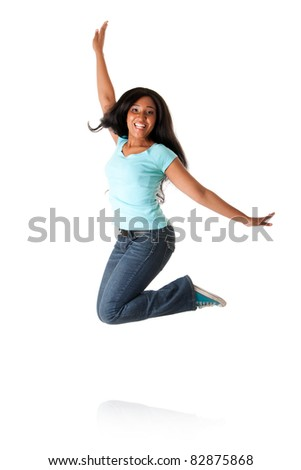 Beautiful happy smiling African Caribbean teenager jumping from happiness to celebrate, wearing blue shirt and jeans, isolated. - stock photo