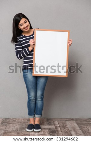 Beautiful happy smiling asian girl in striped jumper looking at camera holding white frame - stock photo