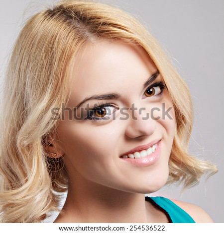 Beautiful happy smiling girl with blond hair, posing in studio on grey background.